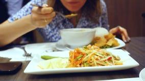 Pasto appetitoso e saporito della donna in caffè tailandese Minestra di riso ed insalata della papaia Immagini Stock