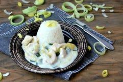 Pasto ceco da carne di pollo, dalla perdita e dalla crema con riso sul piatto scuro sul panno grigio su fondo di legno scuro Immagini Stock