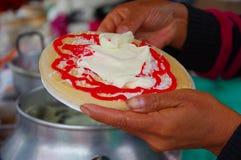 PASTO, COLÔMBIA - 3 DE JULHO DE 2016: mulher que prepara uma sobremesa feita com uma bolacha, um xarope de morango, um coco e um  Foto de Stock