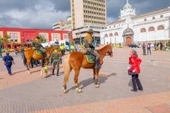 PASTO COLOMBIA - JULI 3, 2016: den oidentifierade kvinnan med ett rött omslag som talar med en polis, monterade på en häst Arkivbild