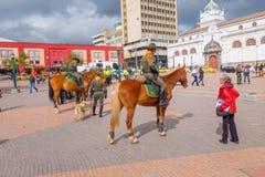 PASTO COLOMBIA - JULI 3, 2016: polisen monterade på en häst som talar på mittfyrkanten av staden Fotografering för Bildbyråer