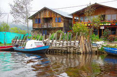 PASTO, COLOMBIA - JULY 3, 2016: blue and white small boat parken infront of some wood houses Stock Photography
