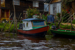 PASTO, COLOMBIA - JULY 3, 2016: colorfull boat parked next to a green canoe infront of some houses in la cocha lake.  stock photography