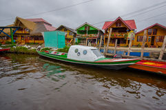 PASTO, COLOMBIA - JULY 3, 2016: small green boat parked next to an orange boat with some shops as background.  royalty free stock photography