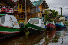 PASTO, COLOMBIA - JULY 3, 2016: some colorfull boats parked next to a shore and some houses in la cocha lake Royalty Free Stock Image