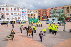 PASTO, COLOMBIA - JULY 3, 2016: some pedestrians walking trough the central square while the police is getting ready for Royalty Free Stock Image