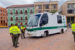 PASTO, COLOMBIA - JULY 3, 2016: unidentified police officers standing next to a police bus parked on the square Royalty Free Stock Photo