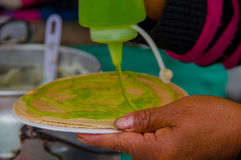 PASTO, COLOMBIA - JULY 3, 2016: woman adding some kiwi syrup to a wafer in a location close to la cocha lake.  royalty free stock image