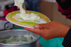 PASTO, COLOMBIA - JULY 3, 2016: woman preparing a dessert made with wafers, kiwi syrup, coconut and cream Stock Image