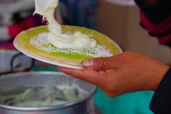 PASTO, COLOMBIA - 3 LUGLIO 2016: donna che prepara un dessert fatto con i wafer, lo sciroppo del kiwi, la noce di cocco e la crem Immagine Stock