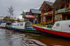 PASTO, COLOMBIA - 3 LUGLIO 2016: le barche del colorfull hanno parcheggiato davanti ai someshopes situati sulla riva del lago di  Fotografia Stock Libera da Diritti