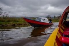 PASTO, COLOMBIA - 3 LUGLIO 2016: uomo non identificato che conduce una piccola barca rossa nel lago di cocha della La Fotografia Stock