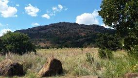 Pasto com rochas e uma montanha foto de stock