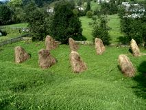 Pasto de la montaña con las pequeñas pilas del heno Fotografía de archivo