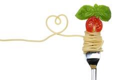 Pasto della pasta delle tagliatelle degli spaghetti con cuore su un argomento di amore della forcella Fotografie Stock