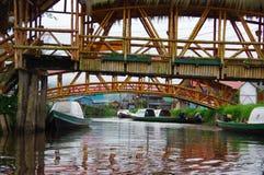 PASTO, KOLUMBIEN - 3. JULI 2016: einige grüne Boote parkten unter zwei Brücken in einem Fluss nah an La cocha See Lizenzfreie Stockfotografie