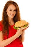 Pasto non sano - la giovane donna felice mangia l'hamburger isolato più Fotografia Stock