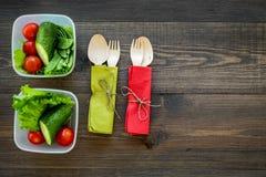 Pasto sano in contenitori Insalata con il pomodoro ed il cetriolo in contenitori sul copyspace di legno di vista superiore del fo Fotografia Stock