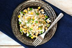 Pasto sano del vegano con riso, i ceci, il mais, i piselli, i fagiolini ed il riso sul piatto scuro sul panno dei jeans su fondo  Immagini Stock