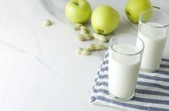 Pasto sano Sia misura e sano Bicchieri di latte sul tovagliolo, mele, arachidi sulla tavola di marmo Toni verdi e blu Copi lo spa fotografia stock libera da diritti
