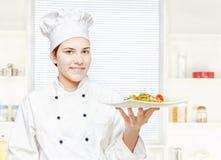 Pasto vegetariano della holding del cuoco unico in cucina fotografia stock