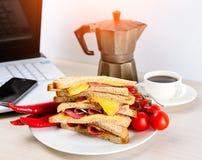 Pasto veloce di sanwich sulla tavola di legno nell'ufficio vicino al computer portatile immagini stock