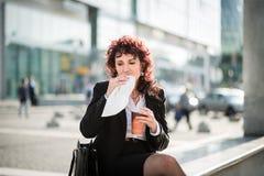 Pasto veloce - donna di affari che mangia in via Fotografie Stock Libere da Diritti
