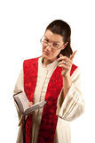Pastor. In white robes with Bible and red stole stock photo
