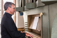 Pastor making music playing organ in church Stock Image