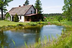 Pastoral rural house in northern Poland. Village landscape, pastoral rural house with barbeque area, northern Poland. Outdoor architecture. Pond reflection stock photo