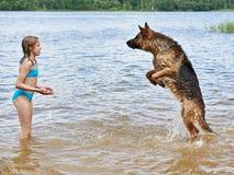 Pastore tedesco e ragazza che giocano nel lago Immagine Stock