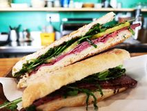 Pastrami sandwich in bar served at the counter with blurred background. royalty free stock photos
