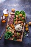 Pastrami, Falafel, babagahanoush, Veggies und Bier in einer Holzkiste, copyspace lizenzfreie stockfotos