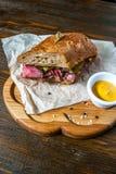 Pastrami kanapka na drewnianym talerzu Zdjęcia Stock