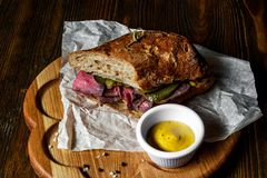 Pastrami kanapka na drewnianym talerzu Zdjęcia Royalty Free