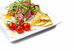 Pastrami Salad. With chips on a white plate shot on a white background Stock Images