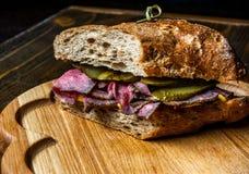 Pastramismörgås på träplattan Royaltyfri Bild