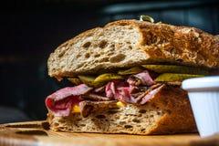 Pastramismörgås på träplattan Royaltyfri Foto