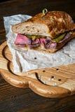 Pastramismörgås på träplattan Royaltyfri Fotografi
