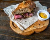 Pastramismörgås på träplattan Arkivbild