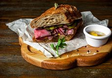 Pastramismörgås på träplattan Royaltyfria Bilder