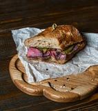 Pastramismörgås på träplattan Arkivfoto