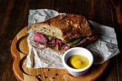 Pastramismörgås på träplattan Royaltyfria Foton