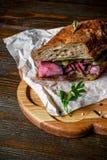 Pastramismörgås på träplattan Arkivfoton