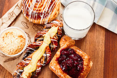 Pastries, buns, custard cake, a glass of milk on the table. Close-up Stock Photos