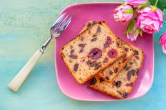 Pastries. A cake slice with fruits on a pink plate. Fruit cake raisin and cherry. royalty free stock image