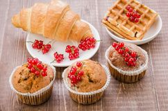 Pastries decorated with red currant/pastries decorated with red currant on a wooden background. Top view. Dessert cake wafers croissant cupcake berry sweet stock image