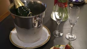 Pastries, glasses and bottle of champagne in ice bucket. Indoors stock footage