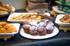 Pastries for guests at a holiday. A variety of pastries for guests at a holiday on a dark table: chocolate cupcakes, decorated with sugar, pies made of puff Stock Photography