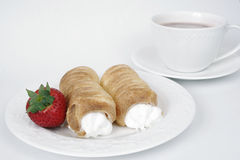 Pastries with hot chocolate. Fresh pastries with hot chocolate and a strawberry Royalty Free Stock Photo